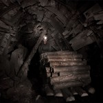 Mineur de charbon ukrainien au fond de la mine poussant un wagon de billes de bois pour faire des étais. Photo Youry Bilak.